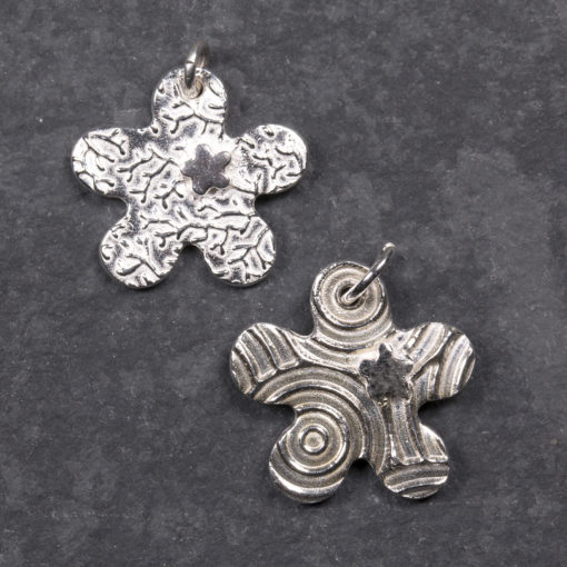 two silver clay flower shapes on a dark background